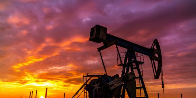 Scenery with oil and gas well pump and dramatic sunset, in East European oil field