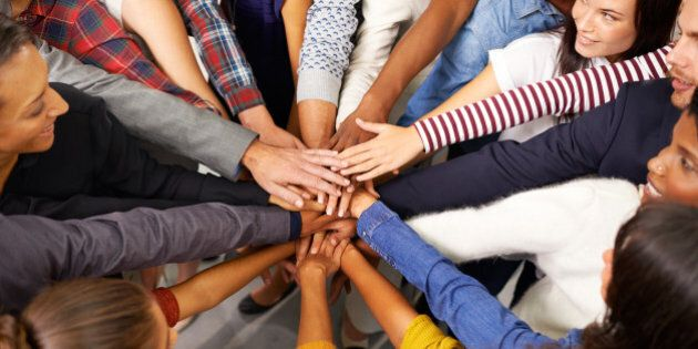 Shot of a diverse group of business people joining their hands in a symbol of