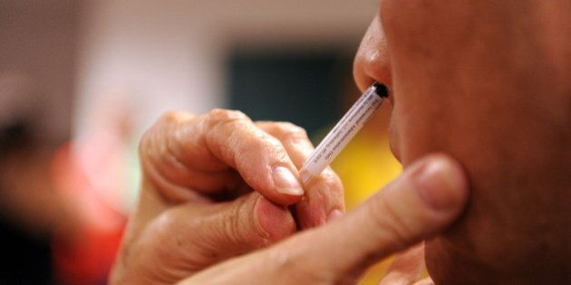A patient receives a nasal spray vaccine during a clinic held by Montgomery County Health and Human Services for the H1N1 virus on October 9, 2009 at the Dennis Avenue County Health Center in Silver Spring, Maryland.    AFP PHOTO / Tim Sloan (Photo credit should read TIM SLOAN/AFP/Getty Images)