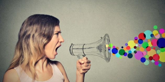 Portrait angry screaming young woman holding megaphone isolated on grey wall background. Negative face...