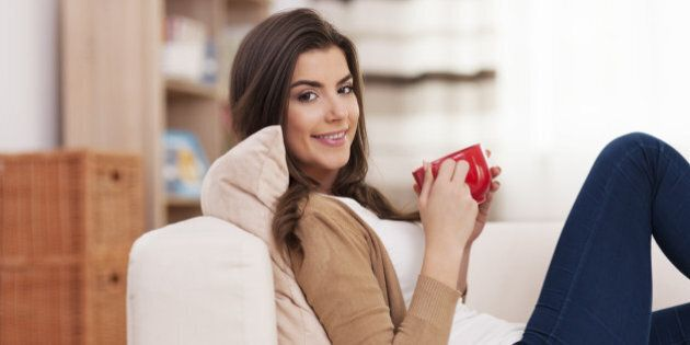 Smiling woman relaxing at home with cup of