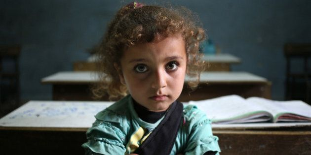 In this picture taken on Thursday, May 29, 2014, a Syrian refugee girl sits in a classroom at a Lebanese...
