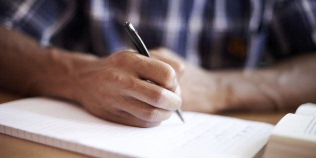 Closeup shot of a young student writing on a note