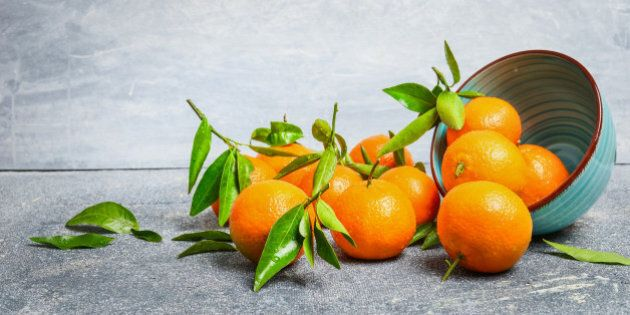 Tangerines with green leaves and bowl on rustic background, side view