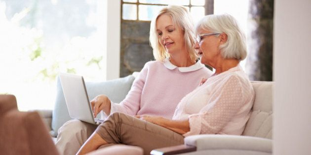 Adult Daughter Helping Senior Mother With Computer At Home