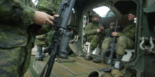 EXERCISE LION ROYAL---11/30/03--Canadian Soldiers clean their weapons prior to going out on patrol in...