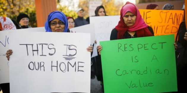 People holds signs during a solidarity march in Toronto November 20, 2015. The march was organized to show solidarity for two Muslim woman were allegedly verbally assaulted on the Toronto subway system on Wednesday, according to local media. REUTERS/Mark Blinch