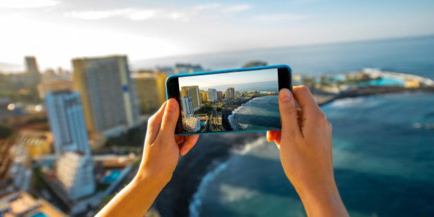 Femaile tourist photographing with smartphone Puerto de la Cruz City on Tenerife