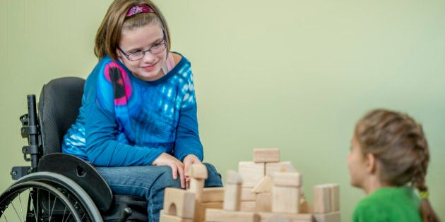 A young handicap girl is sitting in her wheelchair and is playing with other children - they are building...