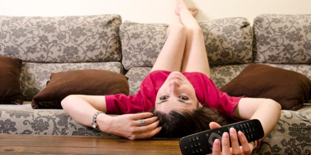 Girl lying facedown watching television