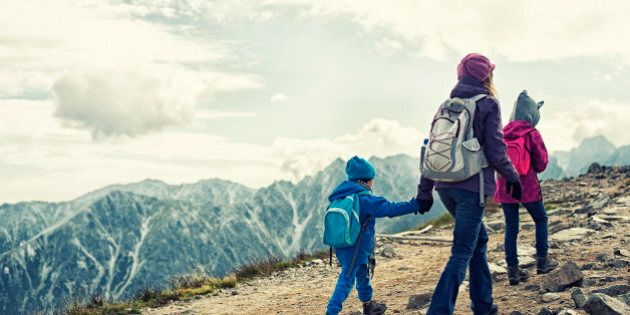 Mother and two kids hiking in mountains. The sky is cloudy. Everybody is wearing a backpacks and warm