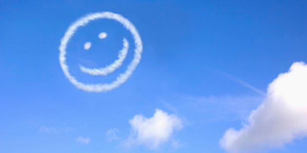 A happy face made from jet trails in a blue sky.