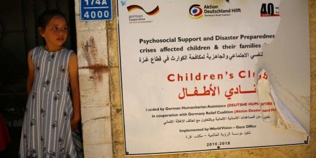 A Palestinian girl stands at the entrance of a project by the Christian charity World Vision, in Beit...