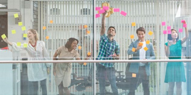 Excited business people with arms raised at window covered in adhesive notes