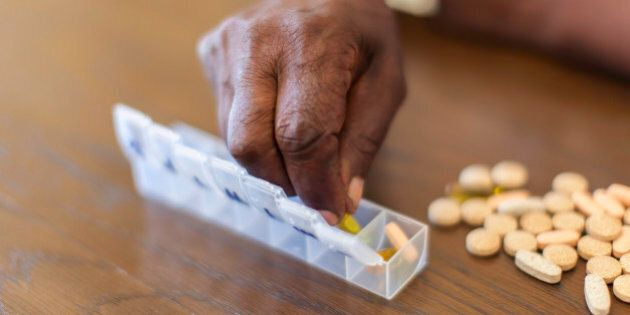 Close up of an african seniors hand placing tablets into a tube. Langebaan, Western Cape, South
