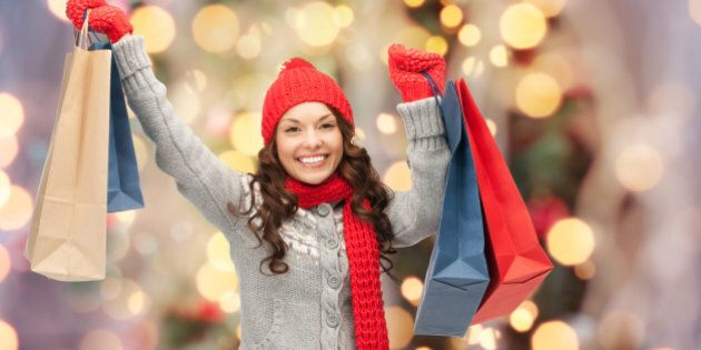 holidays, x-mas, sale and people concept - happy young asian woman in winter clothes with shopping bags...
