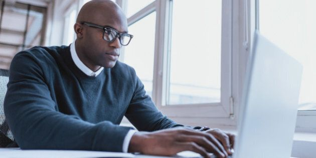 Image of african american businessman working on his laptop. Handsome young man at his