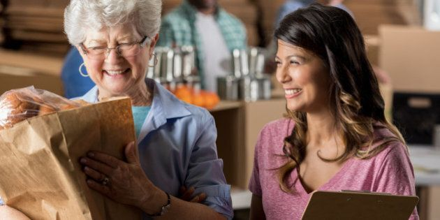Cheerful Hispanic food bank manager helps a senior Caucasian woman. The older woman is carrying a bag...