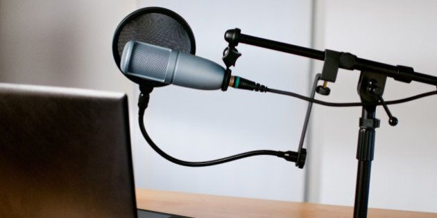 Horizontal image of audio equipment and a laptop sitting on a desk in a small sound room. The studio microphone is on a boom and has a pop filter in place. The laptop is open and ready to use.