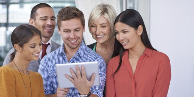 A happy young businessman showing something on his tablet to his coworkers