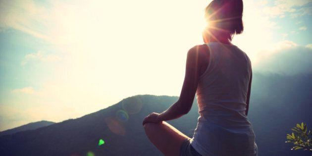 young yoga woman at sunrise mountain peak