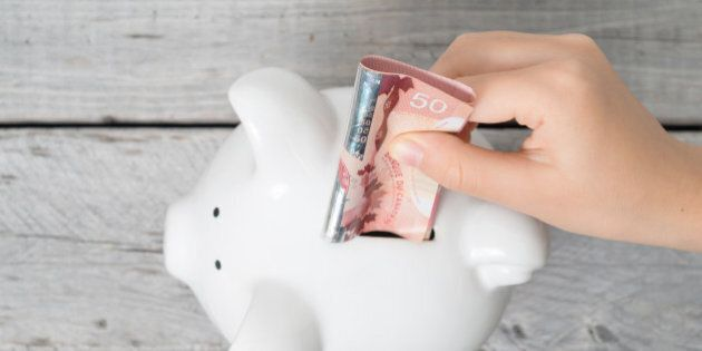 Asian boy hand inserting a fifty dollars bank note into white piggy bank  against wooden grey background