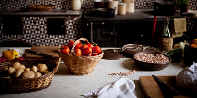 Tomatoes, potatoes, and beans in baskets on a table in a rustic