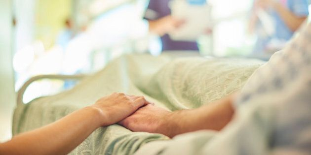 a hospital visitor's hand holds a patient's hand in bed of a hospital ward. In the blurred background...