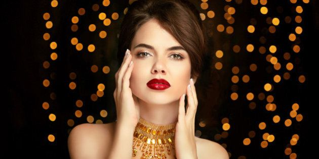 Beauty girl makeup. Fashion jewelry. Elegant lady in golden dress isolated on dark with Christmas party...
