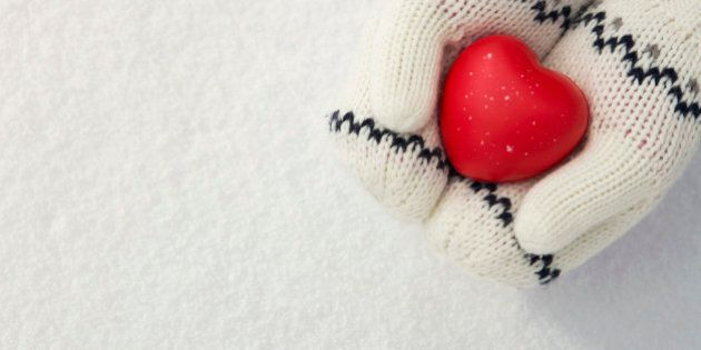 Close up of little girl's hands holding red rubber heart on the snow with copy