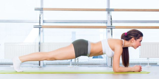 training fitness woman doing plank core exercise working out for back spine and posture Concept pilates