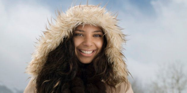 Young woman wearing hooded jacket in snow, smiling, portrait