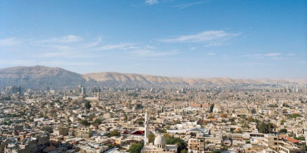 This is a high and wide view of the surrounding neighborhoods of Damascus, Syria. Visible are the rooftops...
