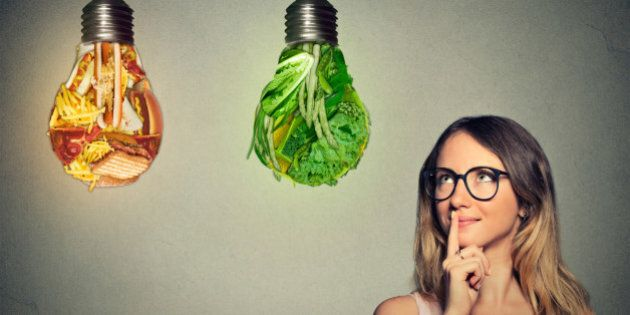 Portrait beautiful woman in glasses thinking looking up at junk food and green vegetables shaped as light bulb isolated on gray background. Diet choice right nutrition healthy lifestyle concept