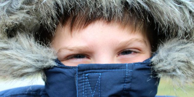 Little boy bundled up in a blue winter coat with fake fur trim around the hood. Winter. Childhood.