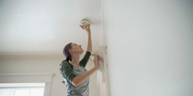 Woman testing smoke detector on ceiling