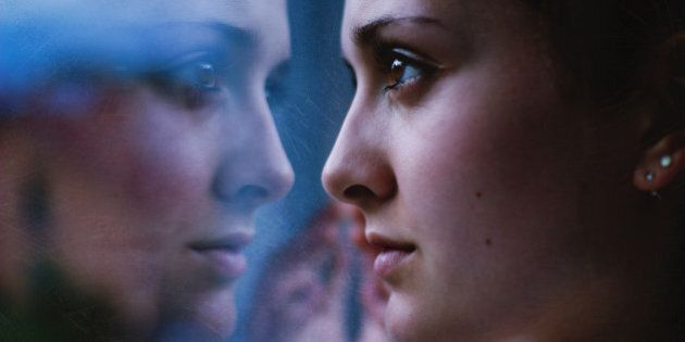 Woman's face close up, staring in mirror with reflection.