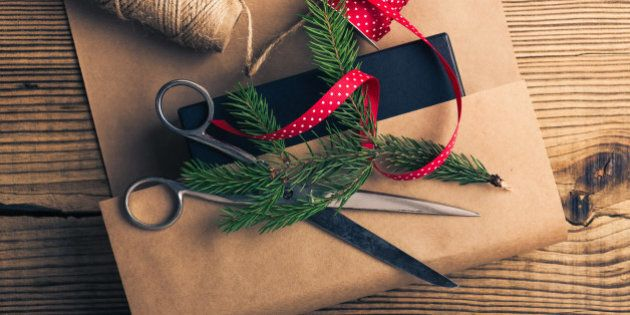 Christmas gift, wrapping craft paper and accessories on wooden table viewed from above