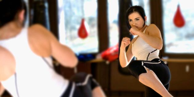 young woman doing kickboxing exercise in front of