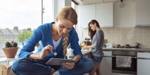 Roommates lifestyle. Young woman using a digital table while her friend washing dishes in the