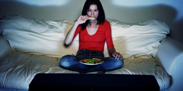 Young woman eating and watching
