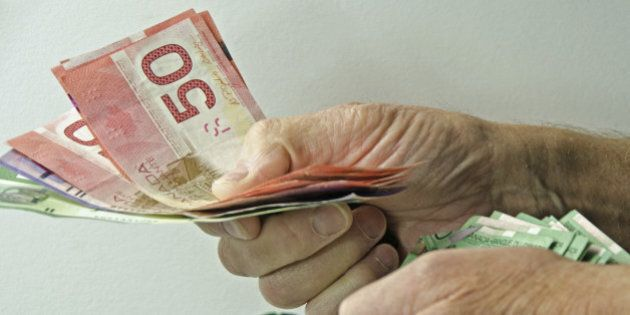 'A man's hands with a large amount of Canadian money handing it out to someone. Money for