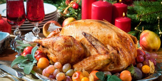 Roasted turkey on holiday table, candles and Christmas tree with