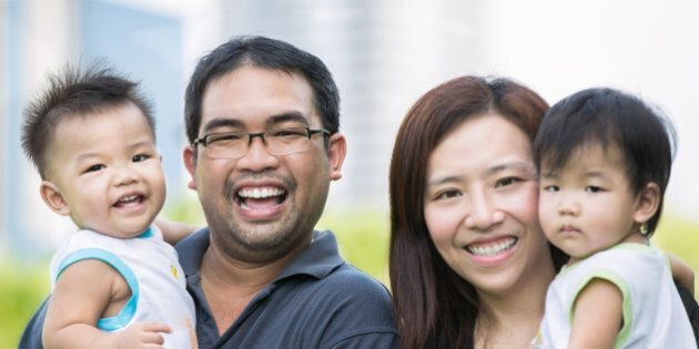 Happy asian mother, father and twins child in the
