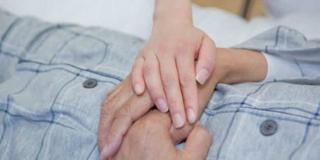 Nurse holding senior man's hand, Kanagawa Prefecture, Honshu,