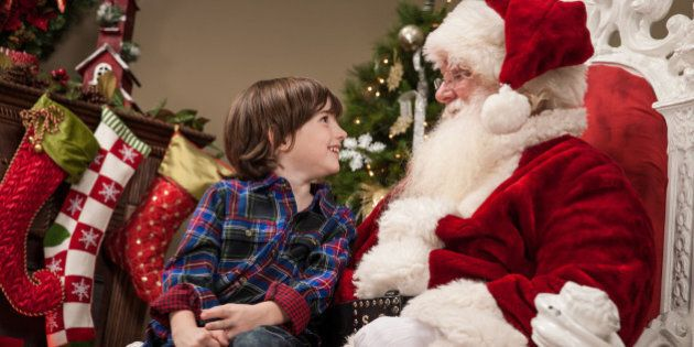 An excited young boy sits on Santa Claus' lap, looking up at him in awe, as they talk together.