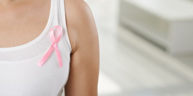 Cropped image of woman wearing pink ribbon, symbol of breast cancer awareness