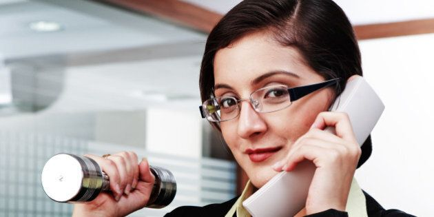 Businesswoman exercising with dumbbells while speaking on telephone