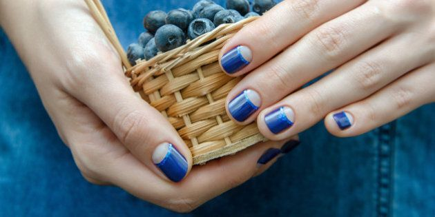 Female hand with blue nail design holding a small basket with