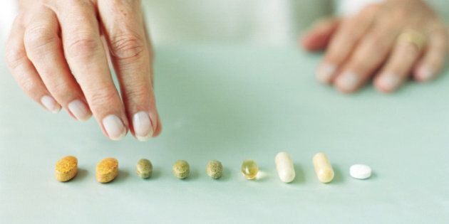 Mature woman arranging pills in